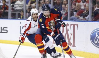 Florida Panthers defenseman Aaron Ekblad (5) and Washington Capitals center Brooks Laich (21) battle for the puck during the first period of an NHL hockey game, Thursday, Dec. 10, 2015 in Sunrise, Fla. (AP Photo/Wilfredo Lee)