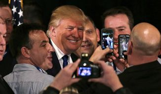 Republican presidential candidate, businessman Donald Trump smiles as he has his photograph taken with supporters after being endorsed at a regional police union meeting in Portsmouth, N.H., Thursday, Dec. 10, 2015. (AP Photo/Charles Krupa)