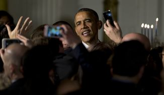 President Barack Obama greets people in the audience during the second of two Hanukkah receptions the East Room of the White House in Washington, Wednesday, Dec. 9, 2015. (AP Photo/Carolyn Kaster)