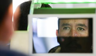 A pedestrian crossing from Mexico into the United States at the Otay Mesa Port of Entry has his facial features and eyes scanned at a biometric kiosk in San Diego, in this Thursday, Dec. 10, 2015, file photo. (AP Photo/Denis Poroy)