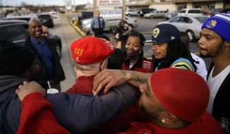 """Secret Santa,"" in red ""Elf"" hat, gets hugs of thanks after handing out several $100 bills along West Florissant Avenue, Wednesday, Dec. 9, 2015, in Ferguson, Missouri. ""Secret Santa"" is an anonymous Kansas City-area man who hands out cash to the needy during the holiday season and decided the Ferguson area is one place he wanted to stop this year. (AP Photo/Jeff Roberson)"