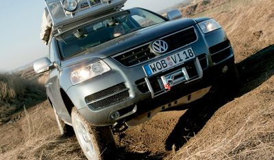 """VOLKSWAGEN TOUAREG is a mid-size luxury crossover SUV produced by German automaker Volkswagen since 2002 at the Volkswagen Bratislava Plant. It was a joint venture project developed by Volkswagen Group, Audi and Porsche. The goal was to create an off-road vehicle that could handle like a sports car. The team, with over 300 people, was led by Klaus-Gerhard Wolpert and based in Weissach, Germany. The result of the joint project is the Volkswagen Group PL71 platform, shared by the Touareg, the Audi Q7 and the Porsche Cayenne, although there are styling, equipment, and technical differences between those vehicles. The Touareg both seat five, while the Q7's stretched wheelbase accommodates a third row for seven passengers. The Volkswagen Touareg is built at the Volkswagen Bratislava Plant in Bratislava, Slovakia, alongside the Audi Q7 and Porsche Cayenne. The Touareg comes as standard with a four-wheel drive system. It has an automatic progressively locking centre differential (with manual override), and a """"low range"""" setting that can be activated with in-cabin controls. Options to make the vehicles more capable off-road include an available 4-wheel AdaptiveAir Suspension (plus Continuous Damping Control) which can raise the car's ride height on command, and an interior switch allowing the rear differential to be manually locked. Its load level ground clearance is at 6.3in, Off Road Level is at 9.6in, and Xtra clearance of 11.8in."""