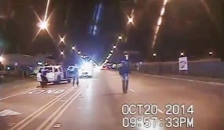 In this Oct. 20, 2014, frame from dash-cam video provided by the Chicago Police Department, Laquan McDonald, right, walks down the street moments before being shot by Officer Jason Van Dyke in Chicago. (Chicago Police Department via AP, File)