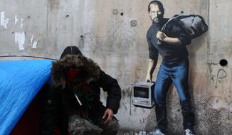A painting by English graffiti artist Banksy is seen at the entrance of the Calais refugee camp in France, Saturday, Dec. 12, 2015. Street artist Banksy has taken on the migrant crisis in a new mural at a migrant camp in France. The elusive graffiti artist has depicted the late Apple guru Steve Jobs — whose biological father was from Syria — carrying a black garbage bag and an early model of the Macintosh computer. His publicist, Jo Brooks, confirmed Saturday that the work found at the encampment in Calais is genuine. (AP Photo/Michel Spingler)