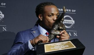 Alabama's Derrick Henry kisses the Heisman Trophy while posing for photos after winning the award as the country's top college football player, Saturday, Dec. 12, 2015, in New York. (AP Photo/Julie Jacobson)