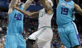 Boston Celtics guard Isaiah Thomas, center, drives to the basket against through the double team  of Charlotte Hornets forwards Cody Zeller,  left, and  P.J. Hairston in the first half of an NBA basketball game Saturday, Dec. 12, 2015 in Charlotte, N.C. (AP Photo/Nell Redmond)