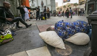 """Star Wars"" fans Deuce Wayne, from Virginia, left, and Larry Ross from La Crescenta, Calif., right, rest while waiting in line up outside the TCL Chinese Theater Imax for the ""Star Wars: The Force Awakens"" premiere in Los Angeles, in this Dec. 9, 2015, file photo. Fans waited in line outside of the historic theater as part of a charity event to raise money for the Starlight Children's Foundation. (AP Photo/Damian Dovarganes, File)"