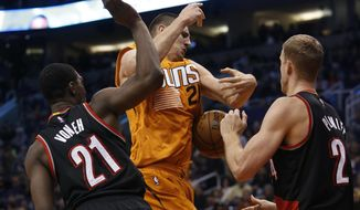 Phoenix Suns center Alex Len (21) battles for the ball with Portland Trail Blazers forward Noah Vonleh (21) and  center Mason Plumlee in the third quarter during an NBA basketball game, Friday, Dec. 11, 2015, in Phoenix. (AP Photo/Rick Scuteri)