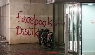 "In this Dec. 12,  2015 picture bicycles stand next to a destroyed  entrance of  a building that was attacked  in Hamburg , northern Germany.  Police say they are looking for a group of up to 20 people who wrote ""Facebook Dislike"" on the social media firm's German headquarters in Hamburg. The unidentified group of people also threw paint bombs and damaged doors and windows at the American company's building in Hamburg's Neustadt neighborhood.  (Bodo Marks/dpa via AP)"