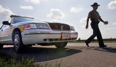 FILE - In this Sept. 15, 2006, file photo, Illinois State Police Officer Sgt. Mike Vorreyer walks from his patrol car to issue a ticket for speeding to a driver on Interstate 72 near Jacksonville, Ill. While the state's sinking fiscal condition has forced belt tightening throughout the state capital in the past two years, the Illinois State Police has spent nearly $8 million to put 300 new vehicles on the road and not a penny of it from tax dollars. (AP Photo/Seth Perlman, File)