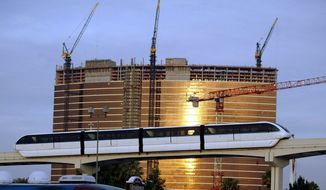 FILE - In an April 20, 2004 file photo, the  Las Vegas Monorail passes the under-construction Wynn Las Vegas hotel and casino in Las Vegas. Transportation leaders in southern Nevada who are considering multiple changes that could cost $7 billion to $12 billion to make it easier for visitors to get around the gambling destination. (AP Photo/Joe Cavaretta, File)