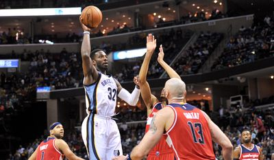 Memphis Grizzlies forward Jeff Green (32) shoots against Washington Wizards forward Otto Porter Jr., center, and center Marcin Gortat (13) the ball against in the second half of an NBA basketball game Monday, Dec. 14, 2015, in Memphis, Tenn. (AP Photo/Brandon Dill)