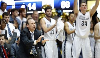 George Washington head coach Mike Lonergan, left, encourages his team during the second half of an NCAA college basketball game against Virginia, Monday, Nov. 16, 2015, in Washington. George Washington won 73-68. (AP Photo/Alex Brandon)