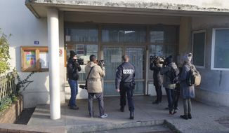 A police enters a preschool, Monday, Dec.14, 2015 in Paris suburb Aubervilliers. French anti-terrorism authorities are investigating an attack Monday on a preschool teacher in a Paris suburb by a masked assailant with a box-cutter and scissors who invoked the Islamic State group. (AP Photo/Michel Euler)