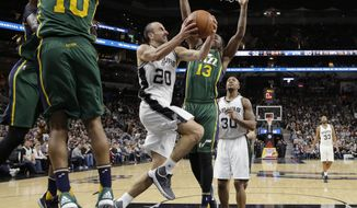San Antonio Spurs guard Manu Ginobili (20) drives between Utah Jazz defenders Alec Burks (10) and Elijah Millsap (13) during the first half of an NBA basketball game, Monday, Dec. 14, 2015, in San Antonio. (AP Photo/Eric Gay)