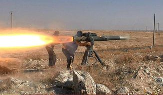 In this image posted online June 26, 2015, by supporters of the Islamic State militant group on an anonymous photo sharing website, Islamic State militants fire an anti-tank missile in Hassakeh, northeast Syria. (militant photo via AP, File)