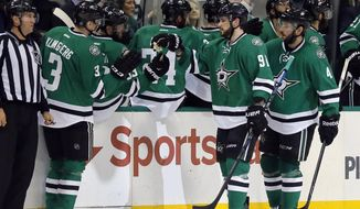 Dallas Stars' John Klingberg (3), of Sweden, and players on thbe bench congratulate Tyler Seguin (91) on his goal against the Columbus Blue Jackets during the second period of an NHL hockey game, Tuesday, Dec. 15, 2015, in Dallas. The score was Seguin's second of the period. Jason Demers trails Sequin. (AP Photo/Tony Gutierrez)