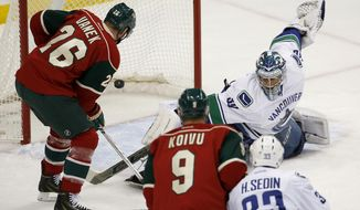 Minnesota Wild left wing Thomas Vanek (26), of Austria, scores on Vancouver Canucks goalie Ryan Miller, right, during the first period of an NHL hockey game in St. Paul, Minn., Tuesday, Dec. 15, 2015. (AP Photo/Ann Heisenfelt)
