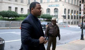 William Porter, left, one of six Baltimore city police officers charged in connection to the death of Freddie Gray, arrives at a courthouse as jury deliberations continue in his trial, Wednesday, Dec. 16, 2015, in Baltimore. Porter faces charges of manslaughter, assault, reckless endangerment and misconduct in office.  (Mark Wilson/Pool Photo via AP)