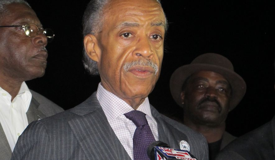 The Rev. Al Sharpton speaks with reporters outside the gates of The Citadel in Charleston, S.C., on Wednesday, Dec. 16, 2015, after meeting with the president of the South Carolina military school. Sharpton discussed the school's response to cadets who were photographed with pillowcases on their heads conjuring the Ku Klux Klan. (AP Photo/Bruce Smith)