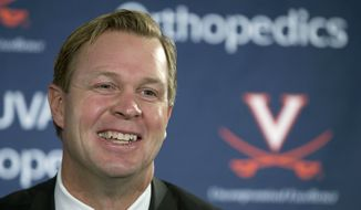 FILE - In this Monday, Dec. 7, 2015 file photo, New University of Virginia NCAA college head football coach, Bronco Mendenhall, smiles during a news conference at the school  in Charlottesville, Va.  Mendenhall takes over after his current team Brigham Young University competes in it's bowl game. Bronco Mendenhall and Kirby Smart are pulling double-duty this month after accepting head coaching positions with other programs. (AP Photo/Steve Helber)