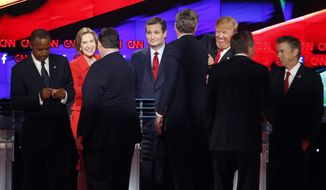 Republican presidential candidates, from left, Ben Carson, Carly Fiorina, Chris Christie, Ted Cruz, Jeb Bush, Donald Trump, John Kasich and Rand Paul talk together following the CNN Republican presidential debate at the Venetian Hotel & Casino on Tuesday, Dec. 15, 2015, in Las Vegas. (AP Photo/John Locher)