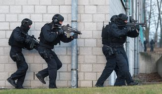 """Members of the new unit """"BFE+"""" of the German federal police exercise in Ahrensfelde, Germany, Wednesday Dec. 16,  2015. Germany on Wednesday introduced a new police unit that officials said will be better armed, outfitted and trained to deal with terrorism, based on an analysis of the country's security in the wake of deadly attacks in Paris earlier this year. (Bernd von Jutrczenka/dpa via AP)"""