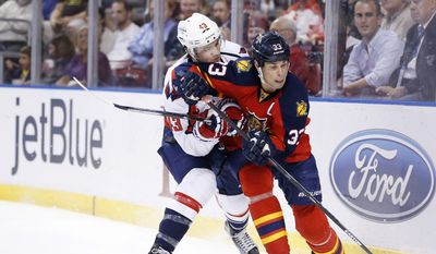 Florida Panthers defenseman Willie Mitchell (33) and Washington Capitals right wing Tom Wilson (43) battle for the puck during the first period of an NHL hockey game, Thursday, Dec. 10, 2015, in Sunrise, Fla. (AP Photo/Wilfredo Lee)