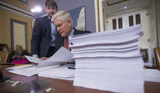 House Rules Committee Chairman Pete Sessions, R-Texas, examines a printout of the $1.1 trillion spending bill to fund the government for the 2016 budget year and extend $680 billion in tax cuts for businesses and individuals, at the Capitol in Washington, Wednesday, Dec. 16, 2015. President Barack Obama is expected to sign the legislation. (Associated Press)