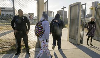 Los Angeles School Police officer Alex Camarillo, far left, and school officials welcome back area students heading back to school at the Edward R. Roybal Learning Center in Los Angeles Wednesday, Dec. 16, 2015. Students are heading back to class a day after an emailed threat triggered a shutdown of the vast Los Angeles Unified School District. (AP Photo/Damian Dovarganes)