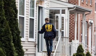 An FBI Joint Terrorism Task Force member enters a home in Harrisburg, Pa., Tuesday afternoon. Dec. 17, 2015, where Jalil Ibn Ameer Aziz, 19, was arrested on charges he attempted to provide support to the Islamic State group. Authorities say Aziz used Twitter to advocate violence against U.S. citizens and military members and to disseminate Islamic State propaganda. Federal prosecutors say a backpack in Aziz's closet contained five loaded high-capacity magazines, a modified kitchen knife, a thumb drive, medication and a balaclava, leading them to suspect he may have been plotting an attack.(James Robinson, /PennLive.com via AP)