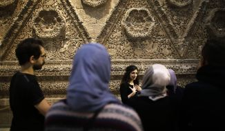 In this Dec. 16, 2015, file photo, Zoya Masoud, center, guides a group of refugees on a special tour through the Museum for Islamic Art, at the Pergamon museum in Berlin. (AP Photo/Markus Schreiber)