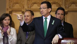 FILE - In this April 4, 2013, file photo, Connecticut Gov. Dannel P. Malloy, second from right, gestures gestures at the conclusion of a legislation signing ceremony as parents of two Sandy Hook shooting victims look on, at the Capitol in Hartford, Conn. Malloy proposed using an executive order to ban gun sales to people on federal no-fly lists. On Tuesday, Dec. 15, 2015, he said he was working with the White House and Justice Department for Connecticut officials to be able to use the watch lists directly, rather than relying on a check conducted through the NCIC process. (AP Photo/Steven Senne, File)