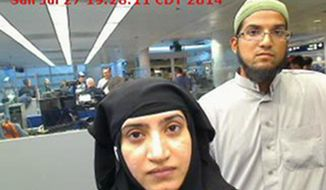 This July 27, 2014, photo provided by U.S. Customs and Border Protection shows Tashfeen Malik, left, and Syed Farook, as they passed through O'Hare International Airport in Chicago. (U.S. Customs and Border Protection via AP)