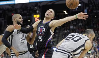 Los Angeles Clippers guard Austin Rivers (25) loses the ball as he is pressured by San Antonio Spurs' Patty Mills (8) and Manu Ginobili (20) during the first half of an NBA basketball game Friday, Dec. 18, 2015, in San Antonio. (AP Photo/Eric Gay)