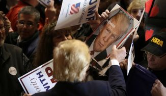 Republican presidential candidate Donald Trump signs autographs during a campaign rally at the Veterans Memorial Building, Saturday, Dec. 19, 2015, in Cedar Rapids, Iowa. (AP Photo/Charlie Neibergall)