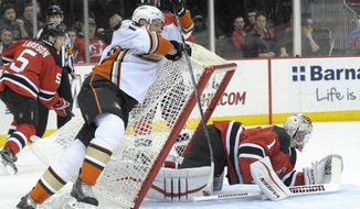 Anaheim Ducks' Corey Perry, left, pulls the net down over Devils goaltender Keith Kinkaid, right, during the first period of an NHL hockey game Saturday, Dec. 19, 2015, in Newark, N.J. (AP Photo/Bill Kostroun)