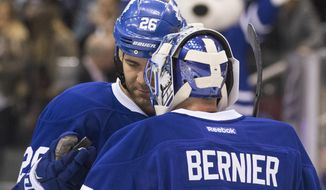 Toronto Maple Leafs' Daniel Winnik hands goaltender Jonathan Bernier the game puck after he shut out Los Angeles Kings in a 5-0 Maple Leafs win in an NHL hockey game Saturday, Dec. 19 2015, in Toronto, (Chris Young/The Canadian Press via AP)