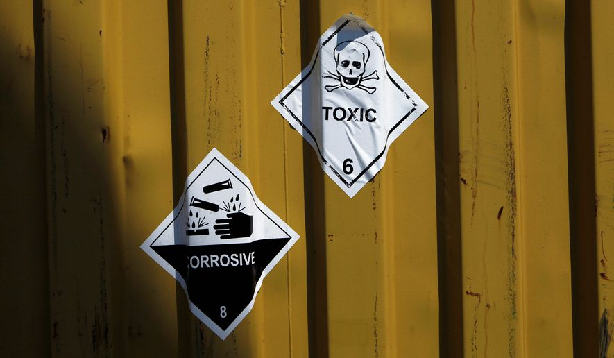 "Signs reading ""Toxic"" and ""Corrosive"" are stuck to containers carrying Syrian chemical weapons aboard the Danish cargo ship Ark Futura in Cyprus coastal waters as they are transported out of the strife-torn country on May 13, 2014. (Associated Press)"