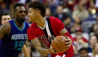 Washington Wizards forward Kelly Oubre Jr. (12), handles the ball against Charlotte Hornets forward P.J. Hairston (19), in the first half of an NBA basketball game at the Verizon Center in Washington on Saturday, Dec. 19, 2015. This was Oubre's first game as a starter. The Wizards won 109-101. (AP Photo/Jacquelyn Martin)