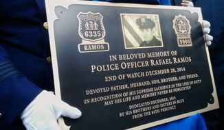 A New York City police officer holds a bronze plaque inscribed with the name of fellow NYPD officer Rafael Ramos, Sunday, Dec. 20, 2015, during a dedication ceremony in the Brooklyn borough of New York. Officers Ramos and Wenjian Liu were fatally shot on Dec. 20, 2014, by a gunman who then killed himself with the same weapon. (AP Photo/Julie Walker)