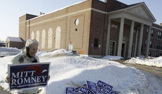 Barbara Kelson carries a Mitt Romney sign past John McCain signs in the snow after a rally for Romney at Elm Street School in Nashua, N.H., on Jan. 6, 2008. (Associated Press)