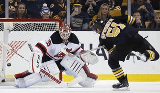 Boston Bruins' Ryan Spooner (51) scores on New Jersey Devils' Cory Schneider in a shootout during an NHL hockey game in Boston, Sunday, Dec. 20, 2015. The Bruins won 2-1. (AP Photo/Michael Dwyer)