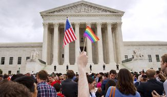 A man holds a U.S. and a rainbow flag outside the Supreme Court in Washington on June 16 after the court legalized gay marriage nationwide. (Associated Press)