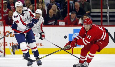 Washington Capitals' John Carlson (74) clears the puck past Carolina Hurricanes' Brett Pesce (54) during the first period of an NHL hockey game, Monday, Dec. 21, 2015, in Raleigh, N.C. (AP Photo/Karl B DeBlaker)