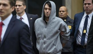 In this Dec. 17, 2015 file photo, Martin Shkreli, the former hedge fund manager under fire for buying a pharmaceutical company and ratcheting up the price of a life-saving drug, is escorted by law enforcement agents in New York after being taken into custody following a securities probe. Shkreli resigned as the head of Turing Pharmaceuticals, one of the companies he runs, and another, KaloBios Pharmaceuticals, said Monday, Dec. 21, in a printed statement that it terminated Shkreli last week.. (AP Photo/Craig Ruttle, File)