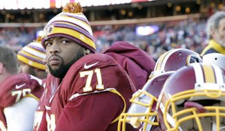 Washington Redskins tackle Trent Williams (71) watches the action from the bench during the first half of an NFL football game against the St. Louis Rams in Landover, Md., Sunday, Dec. 7, 2014. (AP Photo/Mark Tenally)