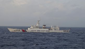 In this photo provided by Japan Coast Guard, an armed Chinese coast guard ship sails in the water near islands, known as the Senkaku in Japanese and the Diaoyu in Chinese, Tuesday, Dec. 22, 2015. It spotted for the first time Tuesday an armed Chinese coast guard vessel near islands at the center of a long-running territorial dispute between the two Asian giants. (Japan Coast Guard via AP)
