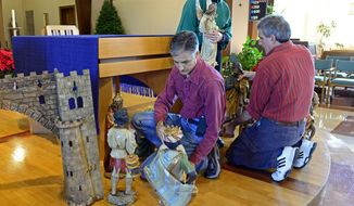 In this Dec. 16, 2015 photo, Barbara Burns and her sons, David, left, and Michael, prepare several of the nativity scene pieces that will be on display at St. Francis Xavier Catholic Church in Carbondale Ill. The Burns family has been instrumental in the preservation and displaying of the 150-year-old nativity scene for decades. (Byron Hetzler/The Southern via AP) MANDATORY CREDIT