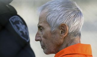 FILE - In this Tuesday, March 17, 2015, file photo, Robert Durst is escorted into Orleans Parish Prison after his arraignment in Orleans Parish Criminal District Court in New Orleans. Prosecutors said on Tuesday, Dec. 22, 2015, fugitive real estate heir Durst has agreed to be extradited from Louisiana to Los Angeles by mid-August to face a murder charge. (AP Photo/Gerald Herbert, File)